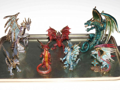 Collection of seven metal dragon ornaments.