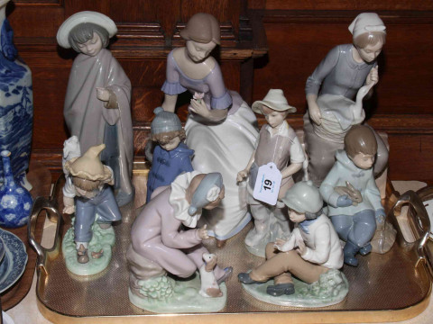 Collection of eight Nao figures and Lladro figure.