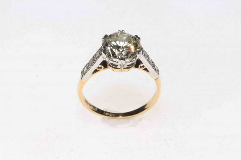 Two carat plus solitaire diamond ring with brilliant shoulders set in 18 carat gold and platinum, size K/L.