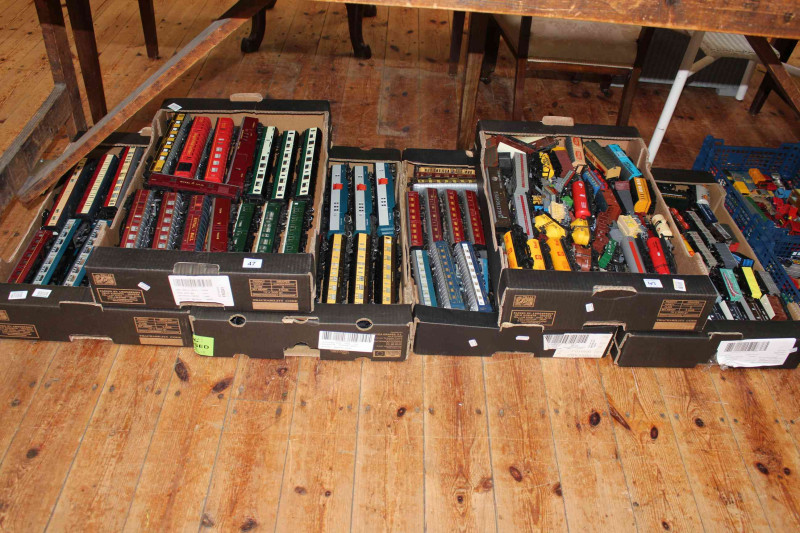 Six boxes of model railway carriages and freight wagons.